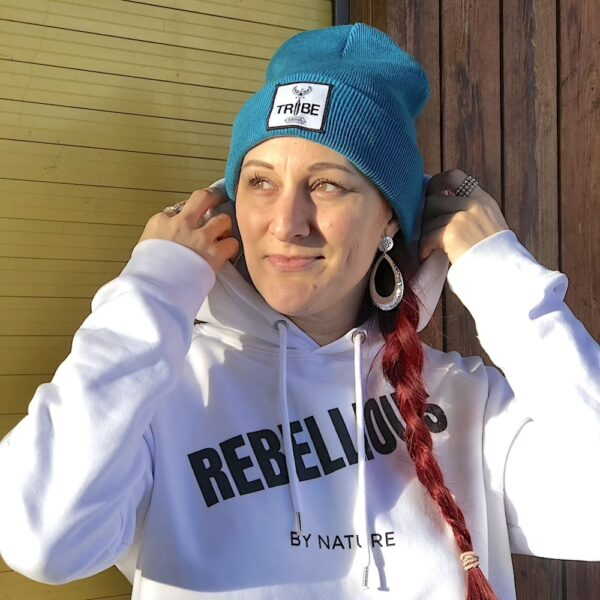Turquoise beanie hat with a white black woven patch saying TRIBE