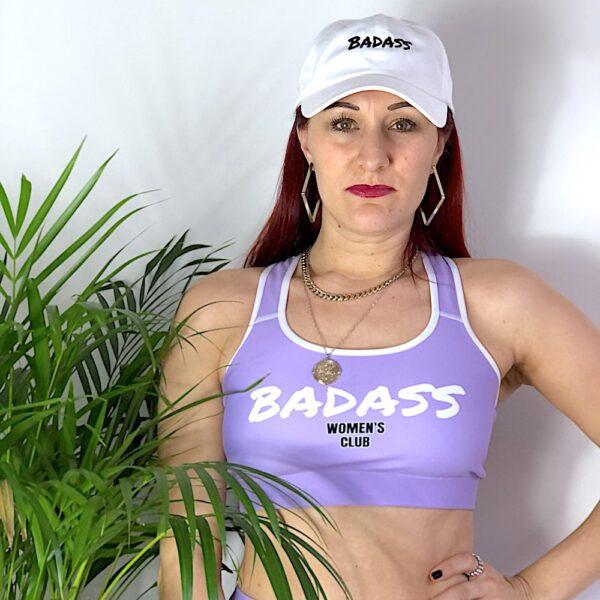 A purple sports bra with a bold white print saying Badass