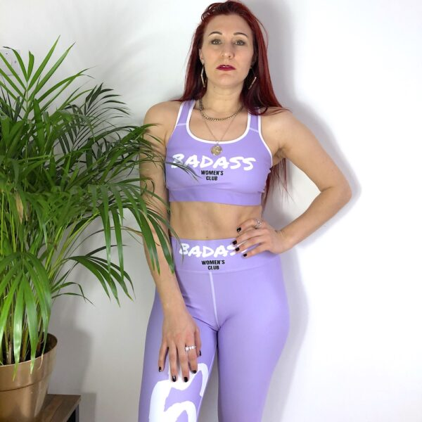 A lavender high waisted yoga leggings with a bold white print saying Badass